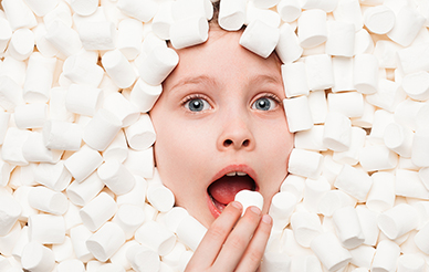 Child surrounded by tempting marshmallows